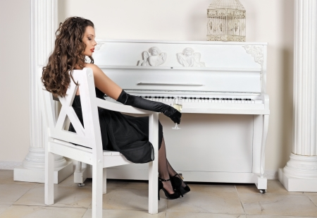The beautiful girl in an evening dress sits on a chair about the white piano Stock Photo