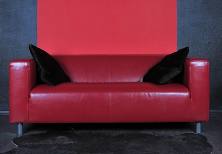 The red sofa in a dark room is put to a wall Stock Photo - 22035434
