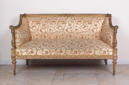 Brown old sofa about a white wall on brown tiled to a floor Stock Photo - 22035478