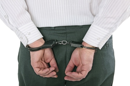 Hands of the man behind the back in handcuffs, isolated on the white background