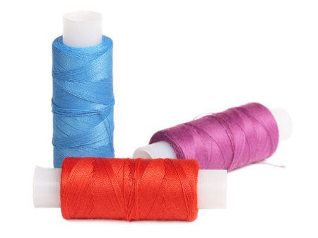 Red, blue and lilac coils with threads, it is isolated on the white photo