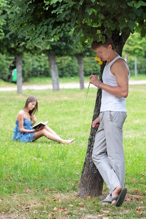 The guy and the girl on a glade in city park photo