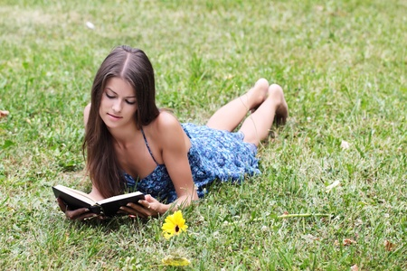 The girl with the book lies on a green grass photo