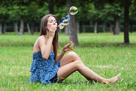 The girl with soap bubbles on a summer glade