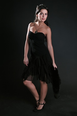 The fine woman in an evening dress on a black background