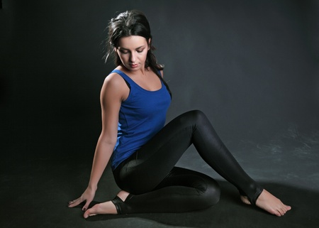 deplorable: The harmonous girl in sportswear sits on a floor against a dark background