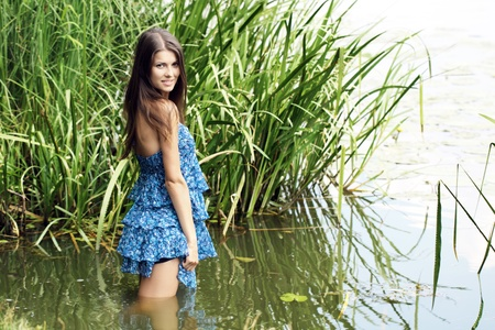 rushy: The girl in a dark blue dress stand knee-deep in water on lake Stock Photo