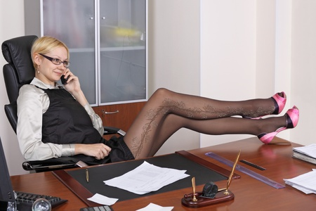 The young girl has relaxed in an armchair at office in the end of the working day photo