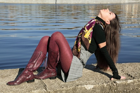 jackboots: The beautiful girl sits on river bank Moscow, has cast away a head back