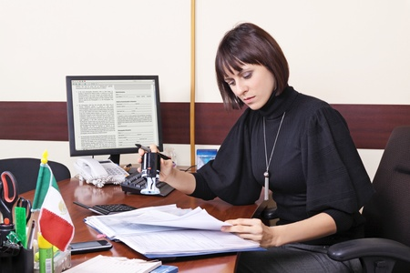 The adult woman the chief works at office behind a table Stock Photo