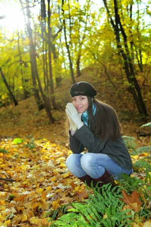 The girl squats in autumn wood in shining sun beams photo