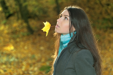 Portrait of the girl with a maple leaf against an autumn landscape photo