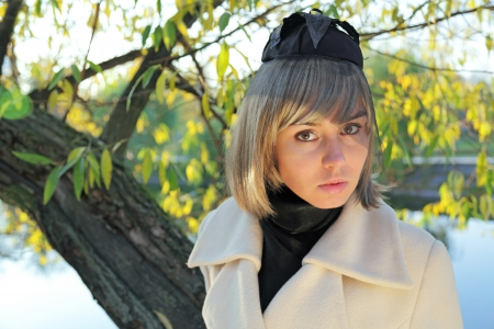The girl in a wig and a black cap with a veil and a white coat against autumn foliage photo