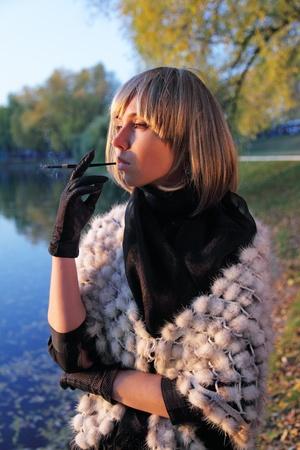 tenedores: La muchacha pensativa en una peluca fuma un cigarrillo sobre un estanque durante una puesta de sol