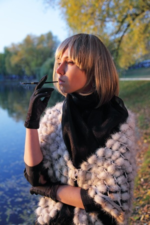 The thoughtful girl in a wig smokes a cigarette about a pond during a sunset photo