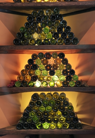 shelfs: The wine bottles which have been laid out by a pyramid on shelfs in a bar Stock Photo