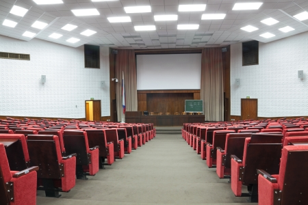 Empty big white conference room with red armchairs