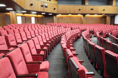 Empty big yellow conference room with red armchairs Editorial