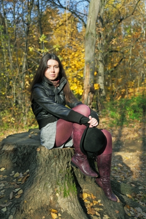 The girl sits on stump in wood photo