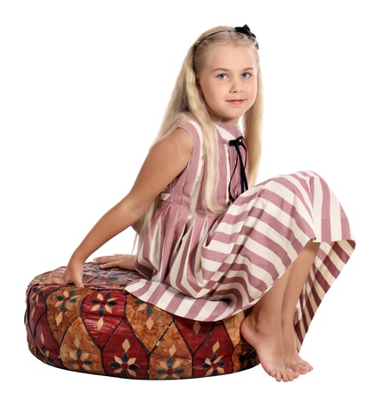 The girl in a striped dress sits on a padded stool, is isolated on a white background