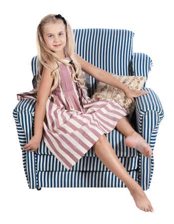 The girl in a striped dress sits on a padded stool, is isolated on a white background photo