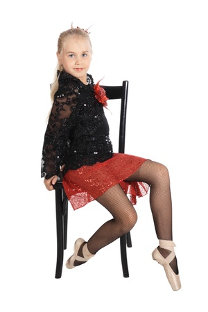 The girl in a red and black dancing suit sits on a chair, is isolated on a white background