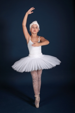 The ten years girl dances in a ballet tutu on a dark blue background photo