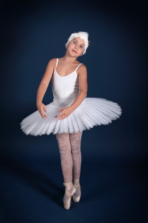 The ten years' girl dances in a ballet tutu on a dark blue background Stock Photo - 25558958