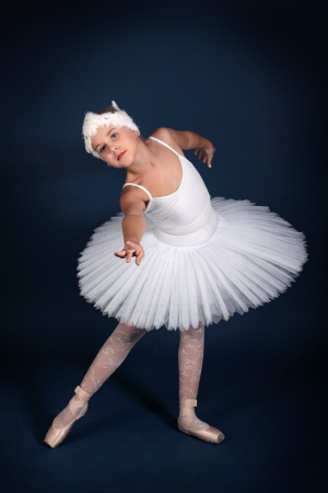 The ten years' girl dances in a ballet tutu on a dark blue background photo