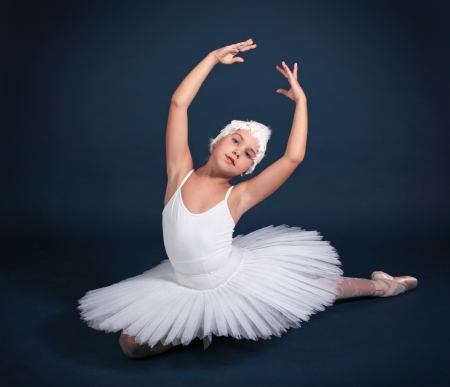 The ten years' girl dances in a ballet tutu on a dark blue background Stock Photo - 25558963