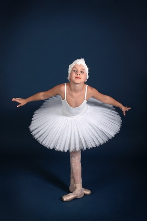 The ten years' girl dances in a ballet tutu on a dark blue background Stock Photo - 25558965