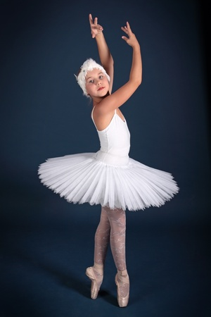 The ten years' girl dances in a ballet tutu on a dark blue background Stock Photo - 25558966