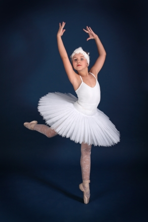 The ten years' girl dances in a ballet tutu on a dark blue background Stock Photo - 25558967