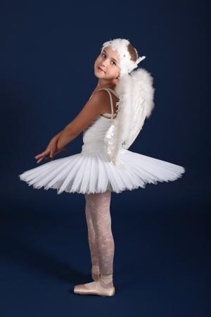 The ten years girl dances in a ballet tutu on a dark blue background