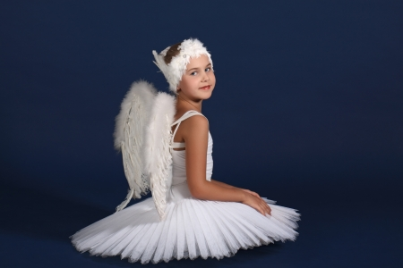 The ten years girl sits in a ballet tutu on a dark blue background photo