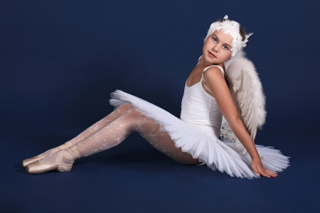 ballerina tights: The ten years girl sits in a ballet tutu on a dark blue background Stock Photo