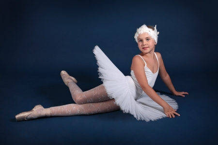 The ten years girl dances in a ballet tutu on a dark blue background photo