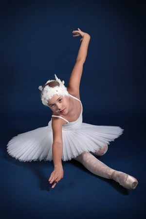 The ten years' girl dances in a ballet tutu on a dark blue background Stock Photo - 25558989