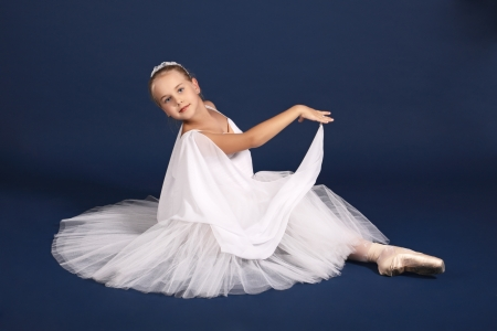 The ten years' girl dances in a ballet tutu on a dark blue background Stock Photo - 25558991