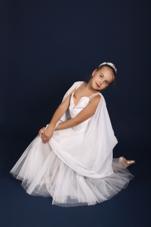 The ten years' girl dances in a ballet tutu on a dark blue background Stock Photo - 25558992