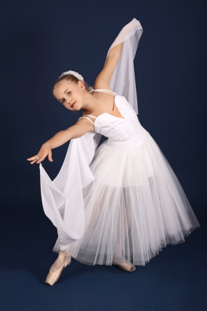 The ten years girl dances in a ballet tutu on a dark blue background