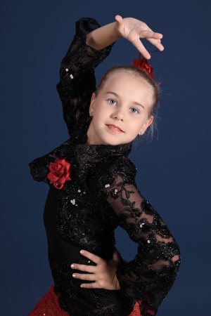 The girl in a red and black dancing suit, on a dark blue background photo