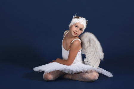 The ten years' girl sits in a ballet tutu on a dark blue background photo