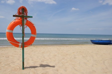 Life buoy on a beach against the sea photo