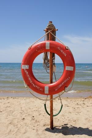 Life buoy on a beach against the sea Stock Photo