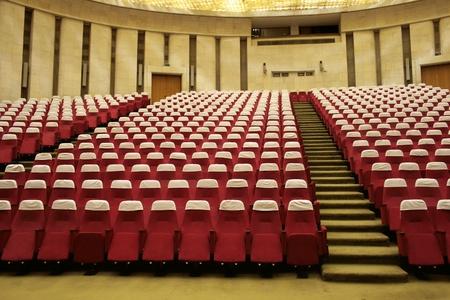 Grande salle de conférence jaune vide avec des fauteuils rouges