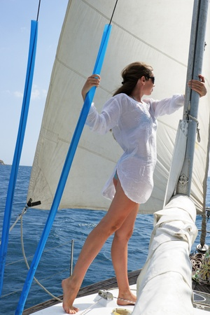undertaken: The girl costs on the yacht undertaken a mast against a sail and the sea