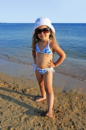 The four-year girl stands against the sea in sun glasses