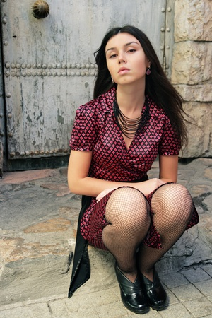 deplorable: The girl in a red dress and stockings sits against an old door