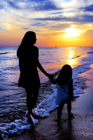 Silhouettes of mum and the little girl against a sea sunset